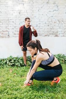 Mujer deportiva estirando en entorno urbano con hombre detrás