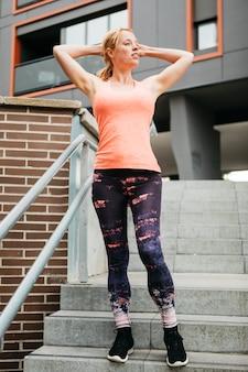 Mujer deportiva estirando en entorno urbano