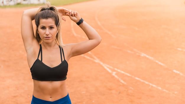 Mujer deportiva estirando en pista de estadio