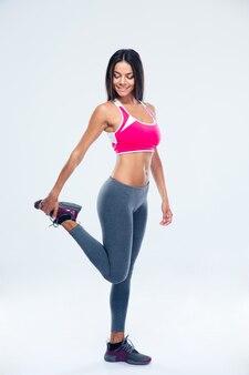 Mujer deportiva feliz estirando la pierna