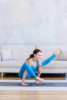 Mujer deportiva flexible haciendo deporte en casa entrenamiento de yoga estiramiento en colchoneta en la habitación