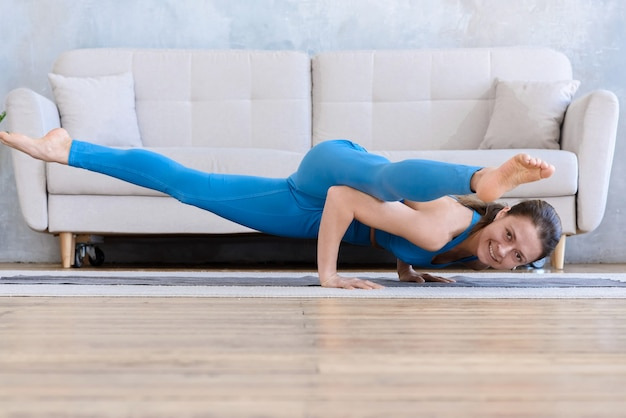 Mujer deportiva flexible haciendo deporte en casa entrenamiento de yoga estiramiento en la estera en la habitación de pie en pose desafiante mirando a la cámara