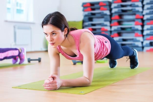 Mujer deportiva en forma haciendo ejercicios de entrenamiento de núcleo de tablones de espalda y músculos de presión