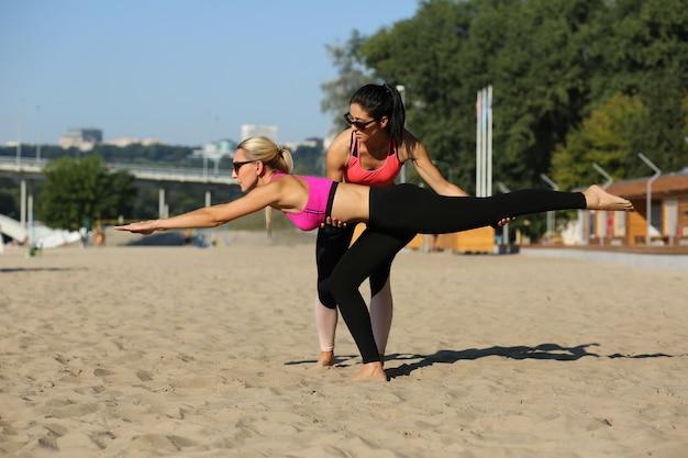 Mujer deportiva haciendo estiramientos con la ayuda de su entrenador personal en la playa.