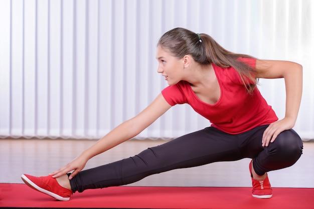 Mujer deportiva hermosa que hace ejercicio en el piso.