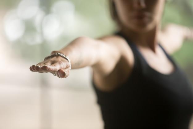 Mujer deportiva joven en la actitud del guerrero dos, fondo del estudio