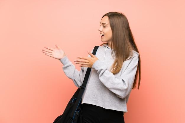 Mujer deportiva joven aislada rosa extendiendo las manos al lado para invitar a venir