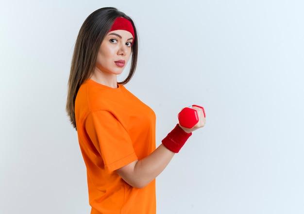 Mujer deportiva joven confiada con diadema y muñequeras de pie en la vista de perfil sosteniendo mancuernas mirando aislado