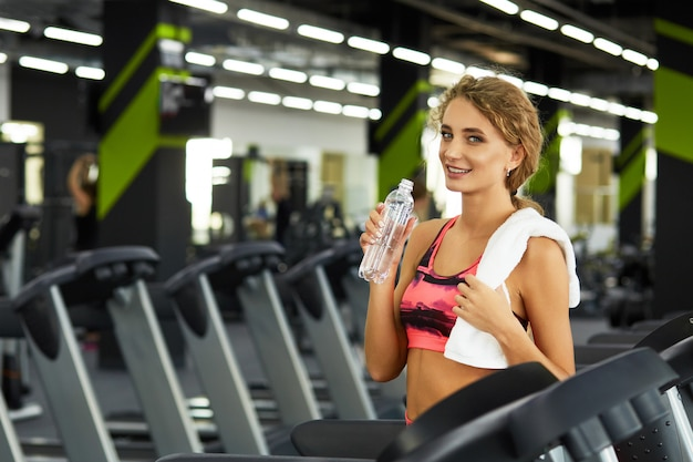 Mujer deportiva joven hermosa que descansa después de entrenamiento duro en gimnasio.
