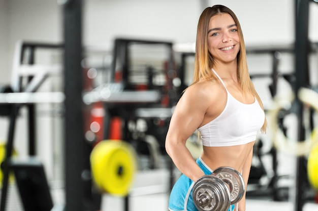 Mujer deportiva con mancuerna