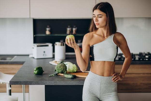 Mujer deportiva con manzana en la cocina