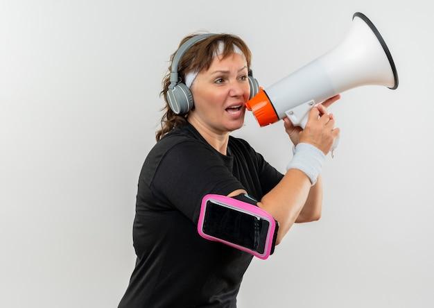 Mujer deportiva de mediana edad en camiseta negra con diadema y auriculares gritando al megáfono con expresión molesta de pie sobre la pared blanca