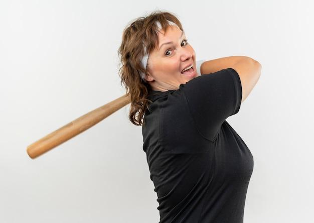 Mujer deportiva de mediana edad en camiseta negra con diadema balanceando un bate de béisbol mirando confiado de pie sobre la pared blanca