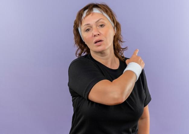 Mujer deportiva de mediana edad en camiseta negra con diadema cansado apuntando hacia atrás de pie sobre la pared azul
