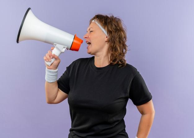 Mujer deportiva de mediana edad en camiseta negra con diadema gritando al megáfono parado sobre la pared azul