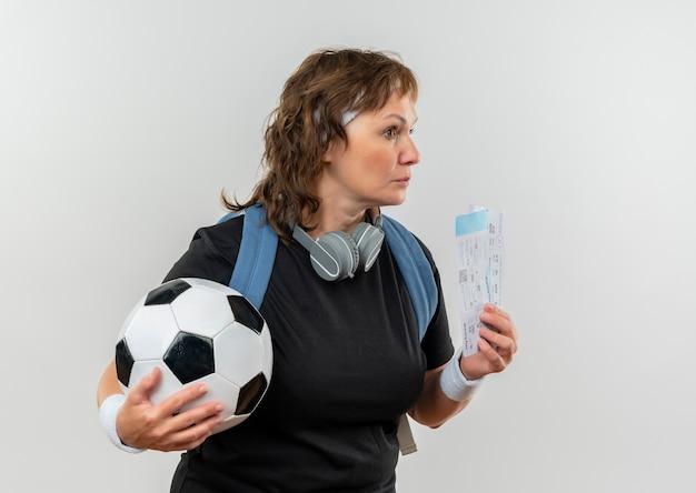 Mujer deportiva de mediana edad en camiseta negra con diadema y mochila sosteniendo boletos de avión y balón de fútbol mirando a un lado con expresión pensativa en la cara de pie sobre la pared blanca