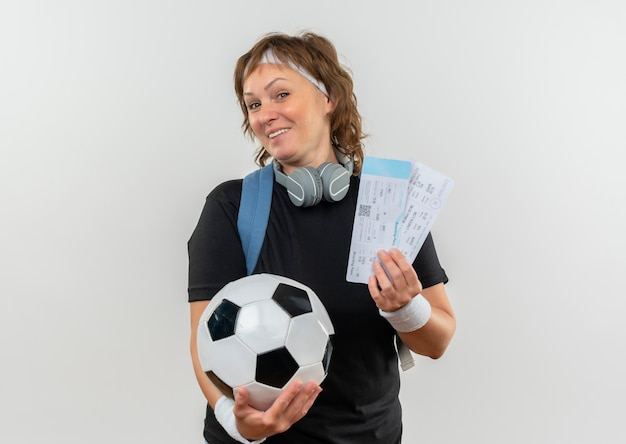 Mujer deportiva de mediana edad en camiseta negra con diadema y mochila sosteniendo boletos de avión y balón de fútbol sonriendo alegremente de pie sobre la pared blanca