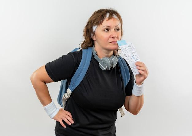 Mujer deportiva de mediana edad en camiseta negra con diadema y mochila sosteniendo boletos de avión mirando a un lado con expresión pensativa en la cara de pie sobre la pared blanca