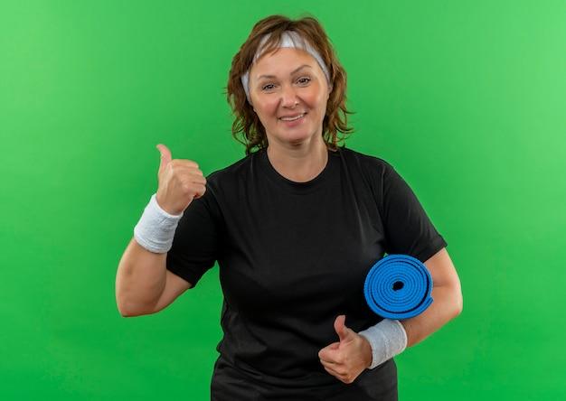 Mujer deportiva de mediana edad en camiseta negra con diadema sosteniendo estera de yoga sonriendo alegremente mostrando los pulgares para arriba de pie sobre la pared verde