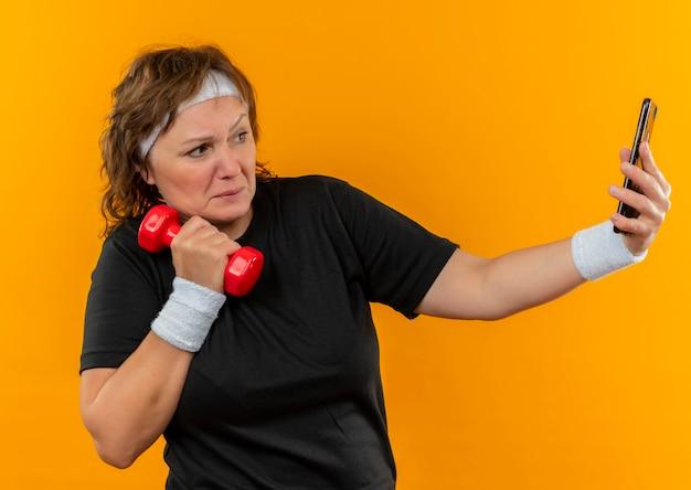 Mujer deportiva de mediana edad en camiseta negra con diadema trabajando con mancuernas de su teléfono inteligente tomando selfie de pie sobre la pared naranja