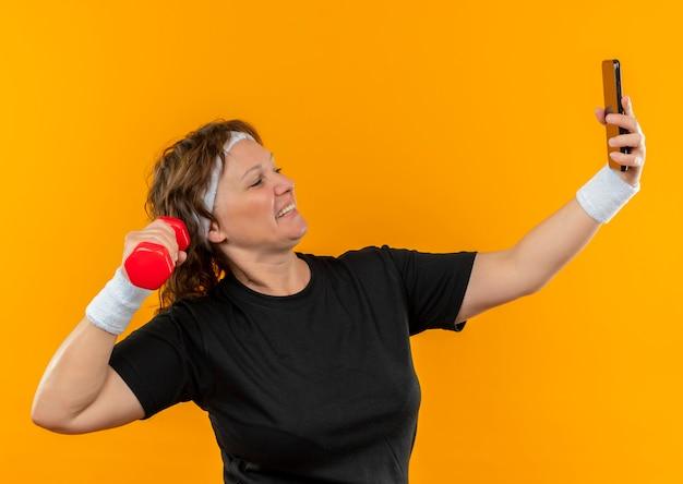 Mujer deportiva de mediana edad en camiseta negra con diadema trabajando con pesas de su teléfono inteligente tomando selfie de pie sobre la pared naranja