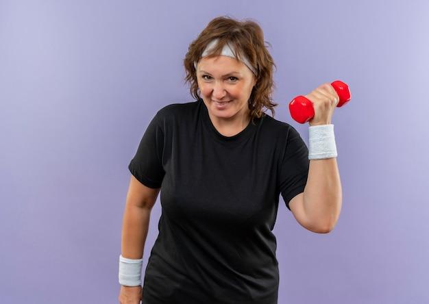 Mujer deportiva de mediana edad en camiseta negra con diadema woking con mancuernas mirando confiado de pie sobre la pared azul