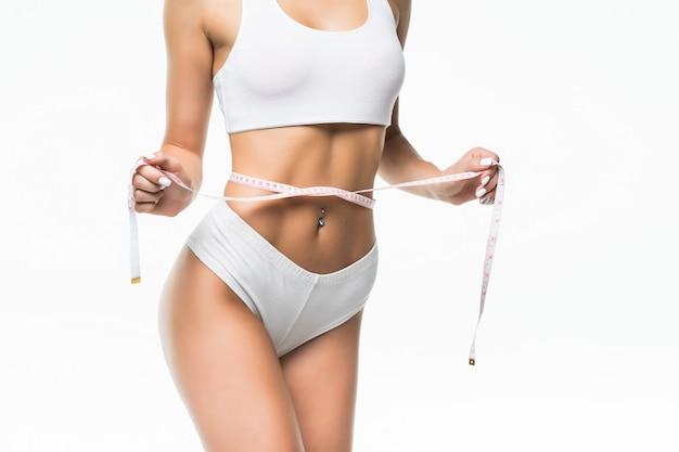 Mujer deportiva y medir alrededor de su cuerpo aislado en la pared blanca