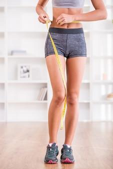 Mujer deportiva y medir alrededor de su cuerpo en casa.