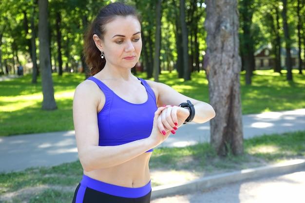 Mujer deportiva mira el reloj en su mano