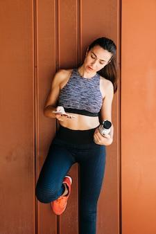Mujer deportiva mirando a smartphone