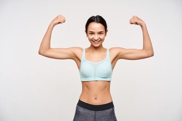 Mujer deportiva morena atractiva joven fuerte sin maquillaje sonriendo alegremente al frente mientras demuestra su poder con las manos levantadas, posando sobre la pared blanca