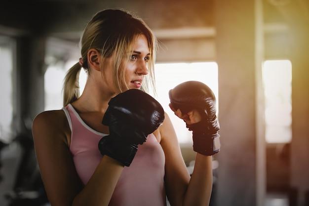 Mujer deportiva de la muchacha hermosa del retrato con los guantes de boxeo traseros que entrena en el gimnasio