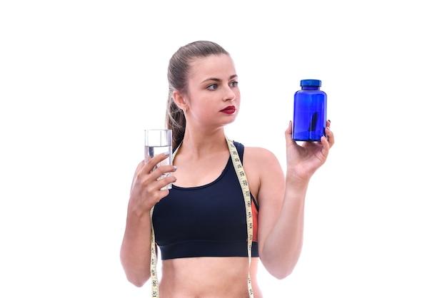 Mujer deportiva con pastillas y botella aislado en blanco