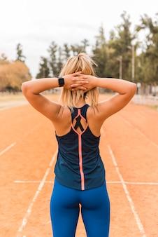 Mujer deportiva en pista de estadio