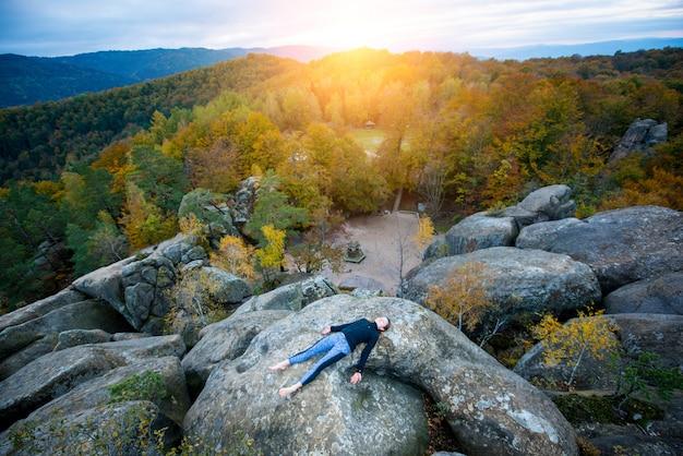 La mujer deportiva está practicando yoga en la cima de la montaña.