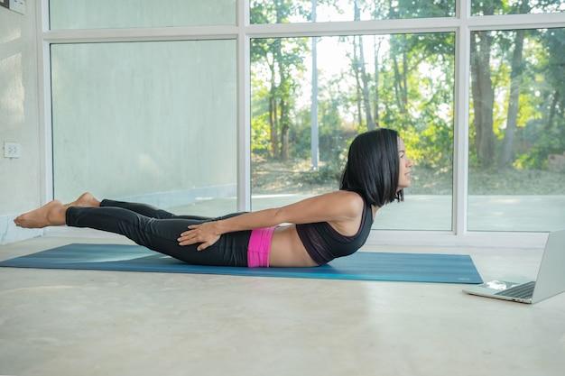 Mujer deportiva practicando yoga, pose de entrenamiento de espalda y glúteos, estiramiento viendo video tutorial de fitness en línea en la computadora portátil, haciendo ejercicio en casa sentado en la alfombra en la sala de estar practicando