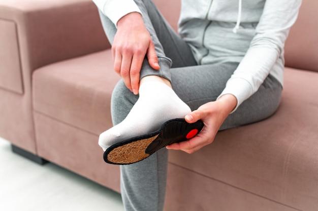 Mujer deportiva que ajusta plantillas ortopédicas en casa. tratamiento y prevención de pies planos y enfermedades del pie. cuidado de los pies, comodidad de los pies. cuidado de la salud, usar zapatos cómodos