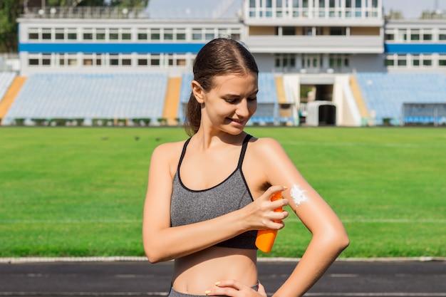Mujer deportiva que aplica la protección solar en estadio antes de correr. deporte y concepto saludable.