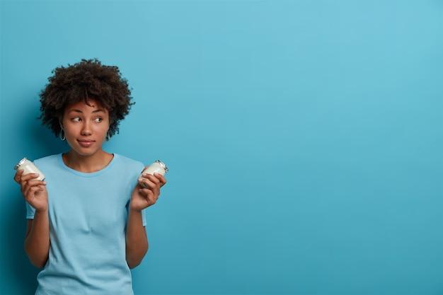 Mujer deportiva saludable con cabello afro sostiene frascos de vidrio de yogur fresco, va a preparar el desayuno, tiene una nutrición adecuada, se concentra a un lado, usa ropa informal, posa contra la pared azul