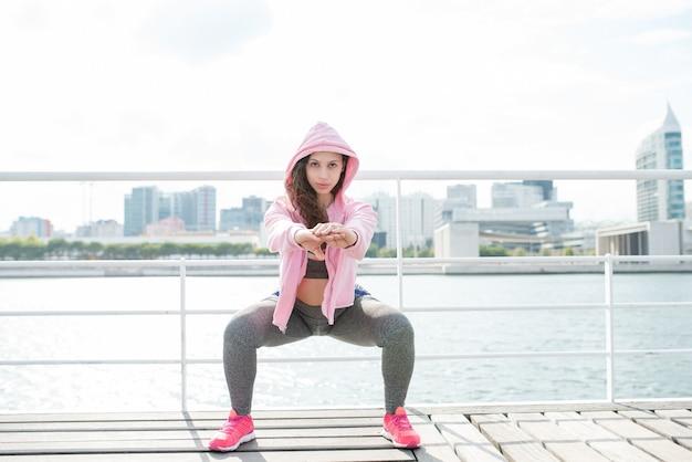 Mujer deportiva seria haciendo sentadillas en el muelle