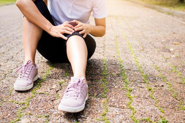 La mujer deportiva tiene dolor de rodilla o lesión en la pierna después de hacer ejercicio en el parque