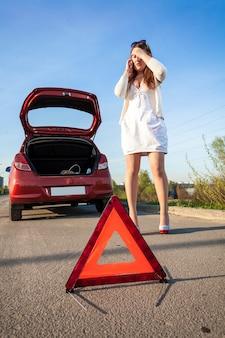 Mujer deprimida llamando al teléfono cerca del coche accidentado