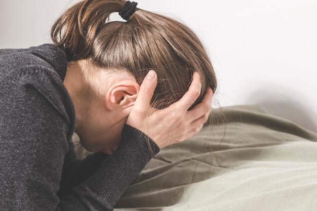 Una mujer deprimida llora con las manos cubriéndose la cara, tendida en el sofá.