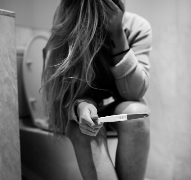 Una mujer deprimida con una prueba de embarazo positiva.