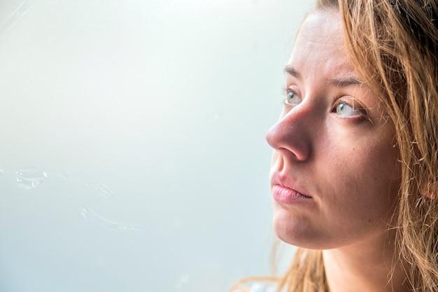 Mujer deprimida. serie. muchacha triste que mira fuera de ventana, vintage filtrada.