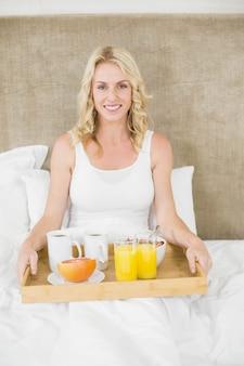 Mujer desayunando en la cama en su habitación