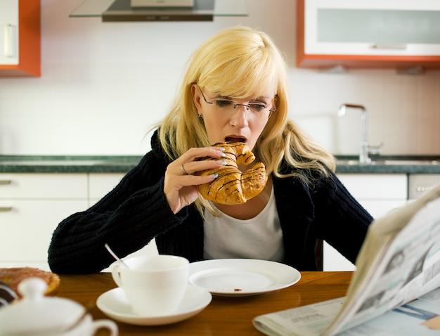 Mujer desayunando y leyendo el periódico