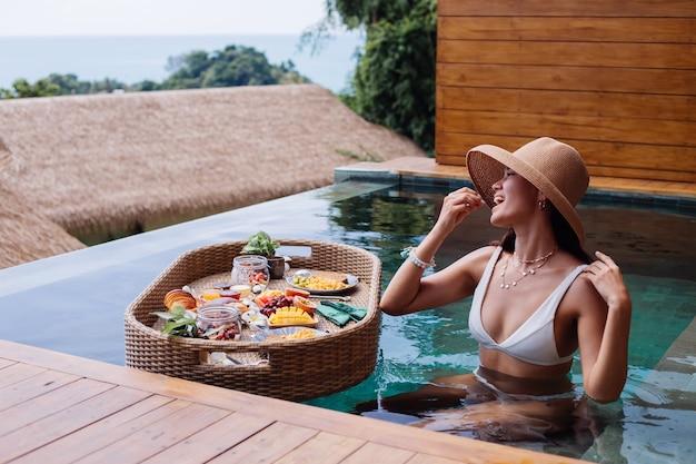 Mujer desayunando tropical saludable en villa en mesa flotante
