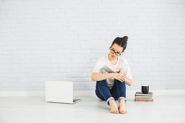Mujer descalza leyendo cerca de la computadora portátil