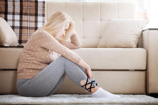 Mujer descalza de mediana edad sentada en el suelo abrazando sus rodillas, cerca del sofá en casa, con la cabeza gacha, aburrida, preocupada por la violencia doméstica.